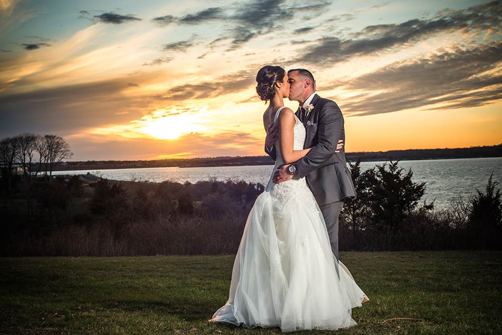 Wedding photography of couple kissing in front of sunset at Oceancliff in Newport, RI
